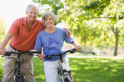 image of elderly couple riding bikes in park
